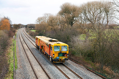 Colas Rail Switch/Crossing Tamper DR73935 passes Hutton Moor on the Weston-super-Mare avoiding line from Bristol Kingsland Road to Exeter St. Davids. Monday 6th January 2014.