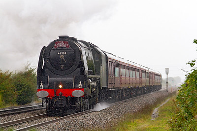 "46233 ""Duchess of Sutherland' powers through the rain at Hewish level crossing heading 1Z43 07.09 Paddington to Kingswear with 47580 dead on the rear. The steam came on the train at Bristol Temple Meads. Saturday 3rd September 2016."