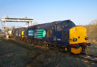 37606 & 37038 sit under the loading gantry at Berkeley with 6M56 to Crewe with one FNA. Wednesday 1st February 2012.