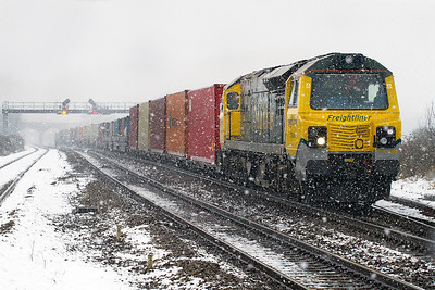 A late running 4O51 09.58 Wentloog to Southampton climbs through the snow at Pilning with 70020 in charge. Wednesday 23rd January 2013.