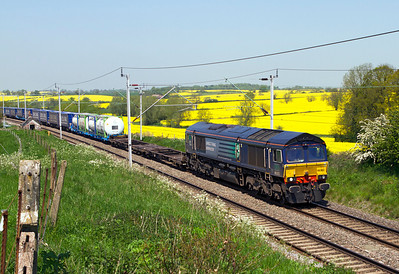 Ex Fastline 66302 heads south through the rape fields at Church Brampton with 4L48 11.16 Daventry to Tilbury. Tuesday 22nd May 2012.