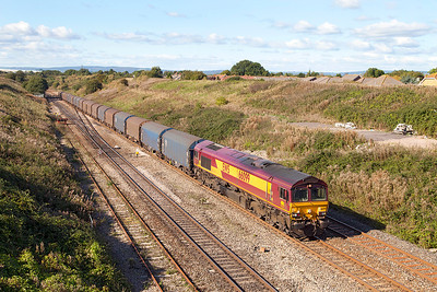 66099 climbs away from the Severn Tunnel past Pilning village with 6032 09.59 Margam to Dollands Moor loaded steel carriers. Thursday 10th October 2013.