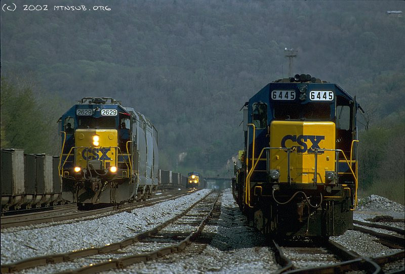 Train time at West Keyser! RIght to left a work train, an arriving empty coal train, and the Luke switcher. April 2002.
