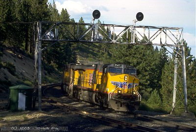A brace of GEs whine downgrade under the Andover signal bridge, taking their train through Tunnel 13 high above Donner Lake.