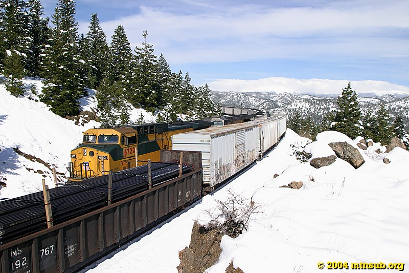 Eastbound coal train meets westbound mixed feight at Crescent siding. View towards the Continental Divide.