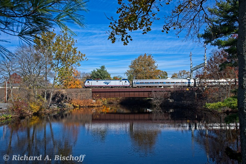 """November 2018. Amtrak """"Sprinter"""" 657 sails across the Wepawaug River bridge in downtown Milford, CT with an """"Amtrak Regional"""" train of Amfleet equipment bound for Washington, DC and perhaps points south. The fall colors are """"past peak"""" but still in evidence. <br /> <br /> My original digital capture, processed with ON1 software."""
