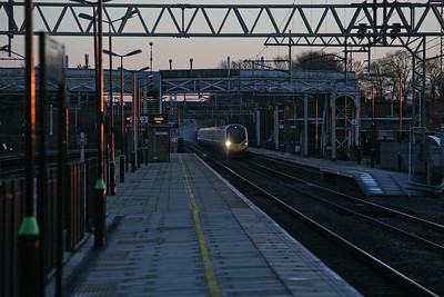 The last rays of afternoon sun light up the gloss black paint of Cheddington station's lamp standards as a Pendolino out of Euston flashes through. 15/11/10