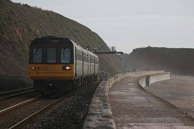 With the wind whipping sand off the beach, 142064 traverses the sea wall section at Dawlish. 6/4/10
