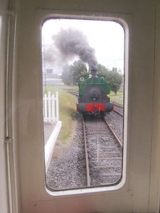 Peckett 1438/1916 seen through one of the end windows of the rolling stock as it runs round at the platform.