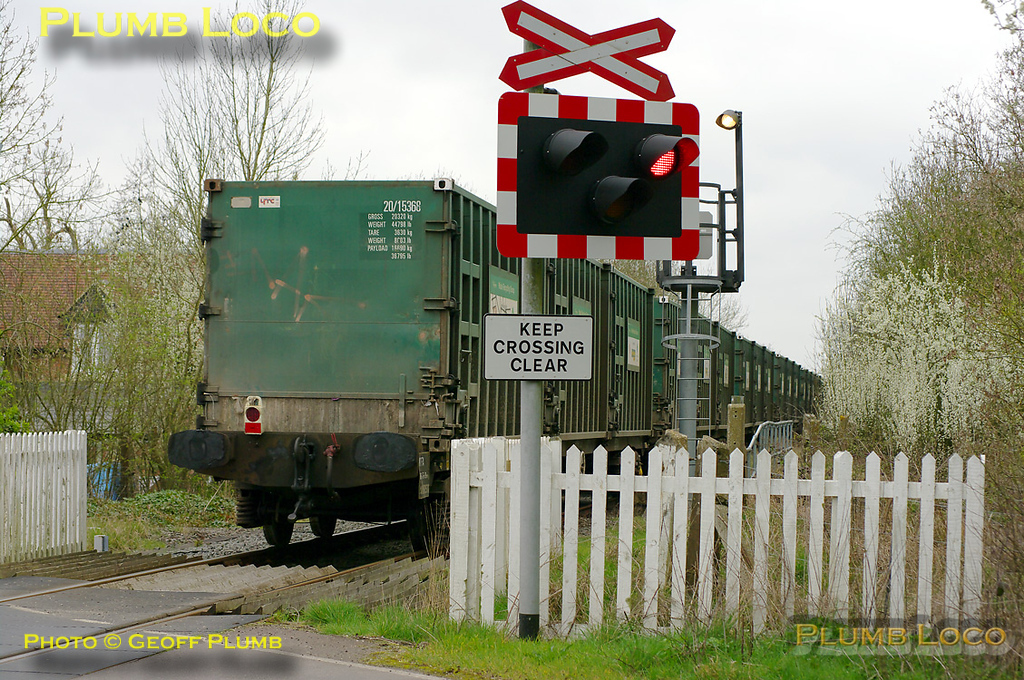 """The end of another era as the last run of 4V60, the empties working of the """"Avon Binliner"""", clears the level-crossing at the site of the former Launton station on the Oxford to Cambridge line at 11:46. This was hauled by 66548 on Friday 1st April 2011. Digital Image No. GMPI8454."""