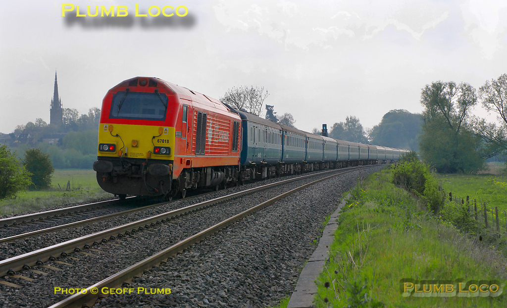 """1Z33 was the 09:15 train from Bolton to Wembley Stadium for the FA Cup Semi-Final match with Stoke on Sunday 17th April 2011. 67027 is leading the train and carrying the """"Bolton Wanderers Supporters Train"""" headboard as it approaches King's Sutton at 12:25. The train consisted of 12 Mk.3 and Mk.2 coaches, all in blue/grey livery with 67018 """"Keith Heller"""" on the rear. This train was also routed via Oxford and the GWML to reach Wembley via Acton Wells and Neasden Junctions. Digital Image No. GMPI8741."""