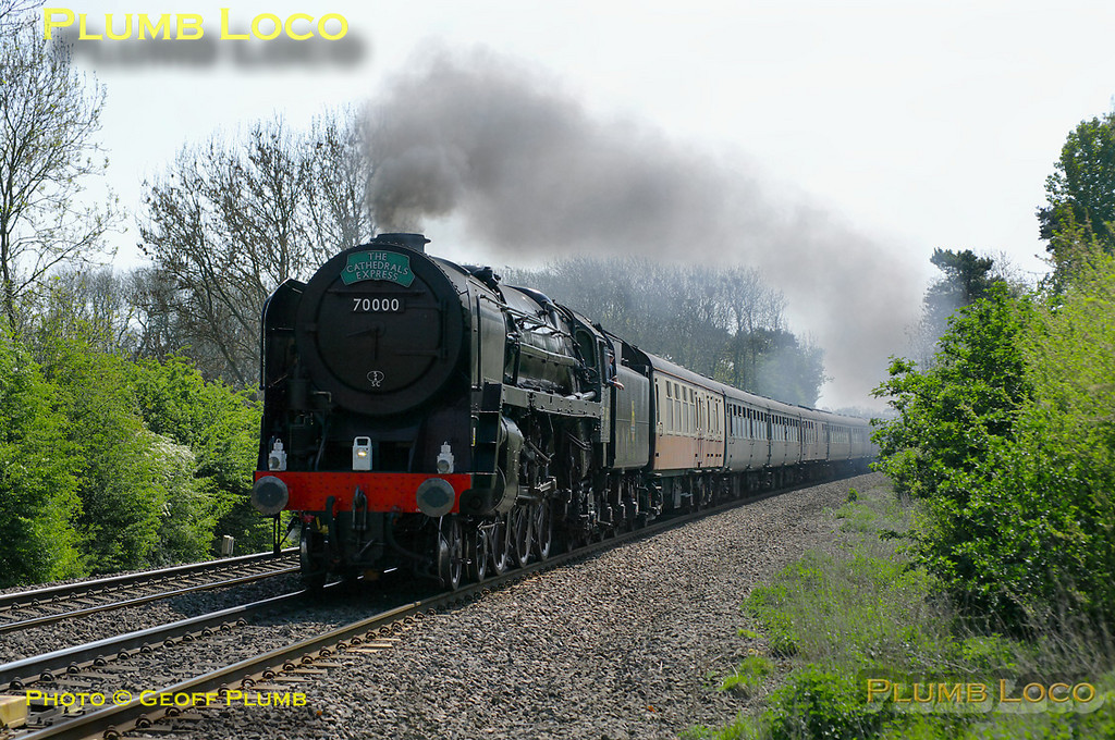 """BR Standard 4-6-2 No. 70000 """"Britannia"""" is hard at work at the head of the 12 coach 1Z40, """"The Cathedrals Express"""", 09:36 from Paddington to Stratford-upon-Avon. It is approaching the foot-crossing at Wormleighton a few minutes early at 12:11 on Saturday 23rd April 2011. This was the hottest day of the year so far, but with the loco working hard and being fired, some visible exhaust is apparent. The loco is still carrying its unlined black livery and is without its nameplates. Digital Image No. GMPI8818."""