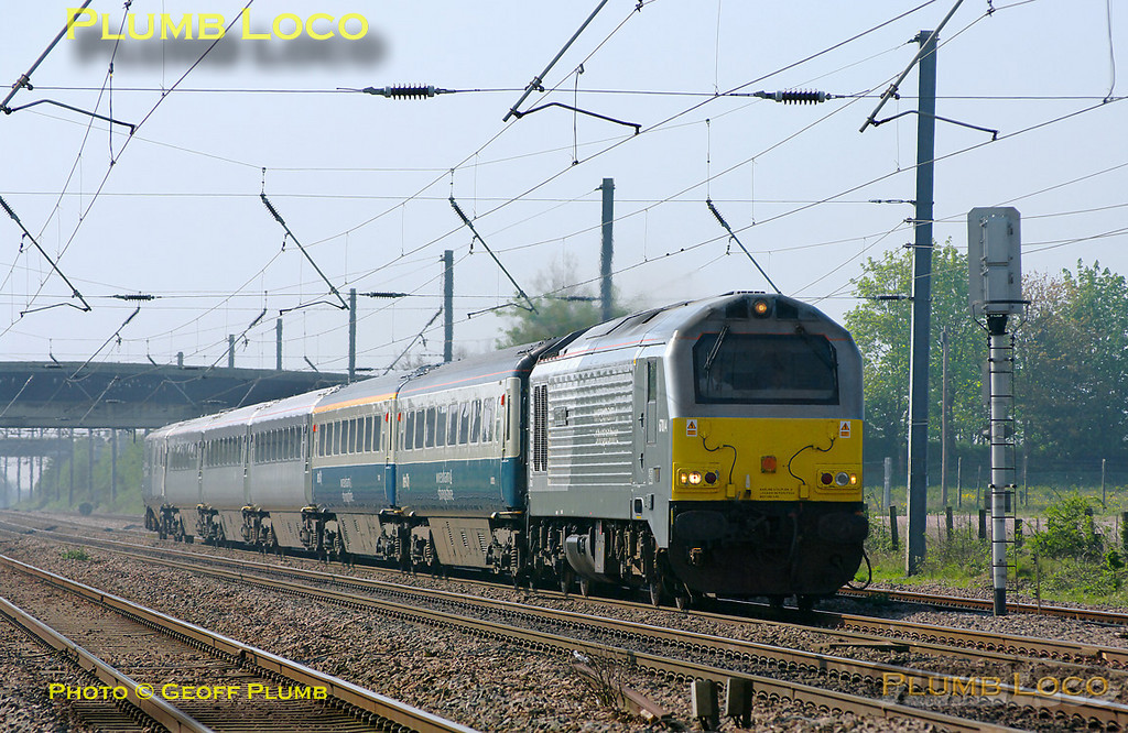 """W&S 67014 """"Thomas Telford"""" is at full speed on the ECML with a mixed set of Chiltern LHCS Mk.3 coaches and DVT 82301 on the rear. This was the 08:30 from Wembley LMD, running as 5E67, to Doncaster Wabtec, where the coaches are to be fitted with plugdoors for future use with Chiltern Railways. The train is approaching the foot-crossing at Langford at 10:18, running around 30 minutes early on Tuesday 19th April 2011. The set consists of two Mk.3 coaches in blue/grey livery with W&S branding, plus two TSOs and an RFM/GFW in debranded W&S silver livery, whether they are to be repainted at Wabtec is perhaps open to speculation! Digital Image No. GMPI8766."""