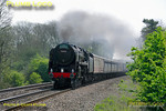 "BR Standard 4-6-2 No. 70000 ""Britannia"" is hard at work at the head of the 12 coach 1Z40, ""The Cathedrals Express"", 09:36 from Paddington to Stratford-upon-Avon. It is approaching the foot-crossing at Wormleighton a few minutes early at 12:11 on Saturday 23rd April 2011. This was the hottest day of the year so far, but with the loco working hard and being fired, some visible exhaust is apparent. The loco is still carrying its unlined black livery and is without its nameplates. Digital Image No. GMPI8816."