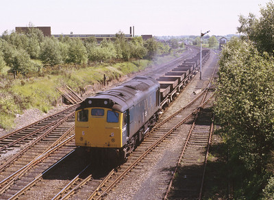 Before virtual quarries were established, fed by massive trains from a handful of super quarries, ballast trains were smaller affairs and would serve a greater number of small terminals around the country. Here we see 25058 passing Cosford loops with empties from Bescot yard to Llanyblodwel. 30/5/85