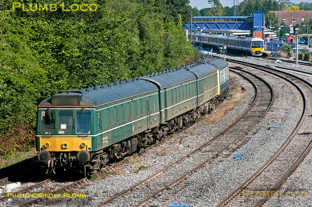 "The Chiltern ""Green Goddess"" former Class 117 RHTT unit No. 960 301 and bubblecar 960 014 have been moved from Aylesbury to temporary stabling in the down CE sidings at Princes Risborough, in order to free up some space at Aylesbury during the first week of blockades of the line further south. This means that units cannot access Wembley depot in the usual way, so more use has to be made of facilities at Aylesbury. 10:42, Friday 19th August 2011. In the background is 165 034 leading a seven coach set, 1V12, the 10:22 from Bicester North to Paddington. Digital Image No. GMPI10081."