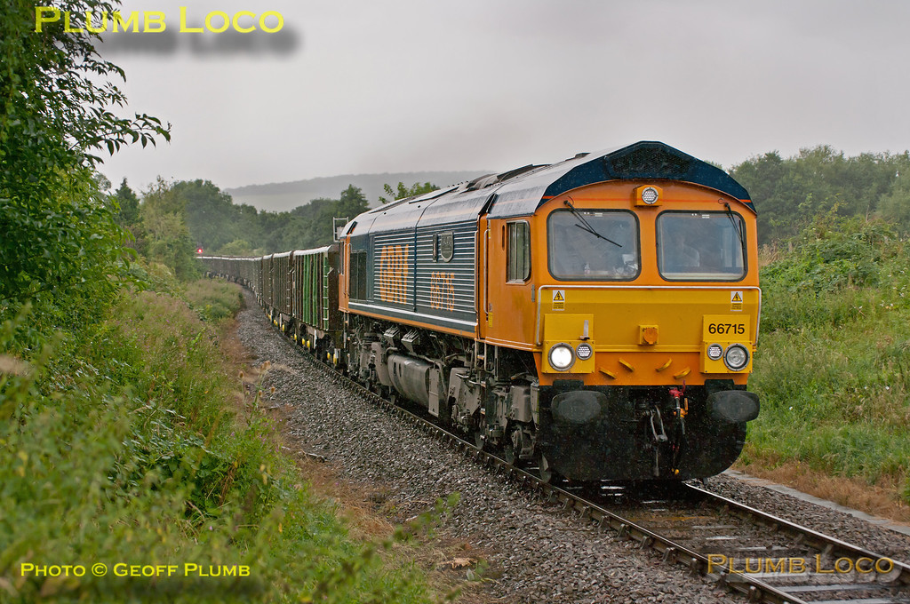 """GBRf 66715 """"Valour"""" is in charge of 6M48, 10:11 from Acton Yard to Calvert with a train of JNA wagons loaded with Crossrail spoil. This was the second of three days due to be run by the train, this time in pouring rain. It is seen approaching the foot-crossing at Park Mill Farm, Princes Risborough, having just branched off the Chiltern main line heading for Aylesbury. 11:32, Wednesday 29th August 2012. Digital Image No. GMPI12427."""