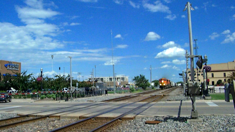 A westbound BNSF manifest freight passes a grade crossing at the old Northern Pacific depot at downtown Fargo, North Dakota. The crossing is a quiet zone - no horn, just double gates and bells. The station, visible at left after panning with the locomotives, is now used by the Fargo Parks Dept., a small museum, and a senior center.