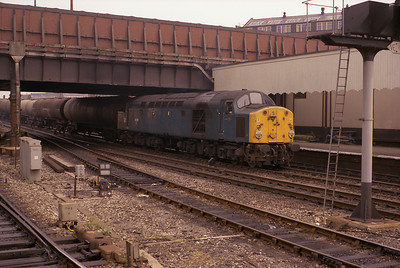 A westbound tank train passes Manchester Victoria behind 40091 20/7/84.