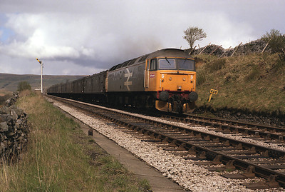 47018 passes Garsdale down distant with a long van train 3/5/87.