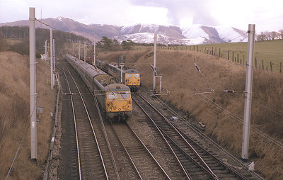 Class 87s were conceived as mixed traffic locos.  On a dull 13/2/87 87029+87014 stand in Grayrigg up loop with a steel coil train from Ravenscraig as an unidentified 87 rushes past with a Glasgow-Euston express.
