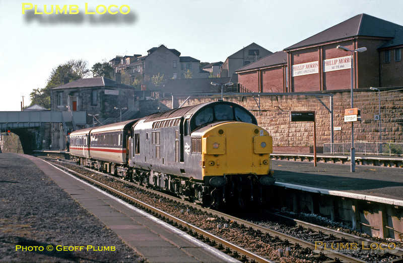 Class 37/0 No. 37087 passes through Springburn station with a couple of newly refurbished Mk.II coaches in tow at 18:25 on the afternoon of Wednesday 8th May 1991. The engine was then in Departmental all-over grey livery. Slide No. 21759.