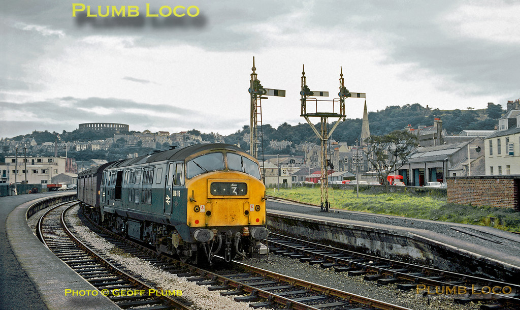 From the Geoff Plumb collection of original slides. The classic view of Oban station, overlooked by McCaig's Tower, with North British Type 2 Bo-Bo diesel No. D6119 about to depart with a train for Glasgow, with a rather interesting leading vehicle. These engines were built in 1959/60 and became Class 21, though this loco was one of the class re-engined with a more powerful Paxman power unit and re-classified Class 29. The class was not a success and all had been withdrawn by 1972. Wednesday 21st August 1968. Photographer unknown. Note the semaphore signals originally supplied by Stevens & Sons, complete with the Stevens Orb Finials, though the original lower quadrant arms have been replaced with newer upper quadrants.
