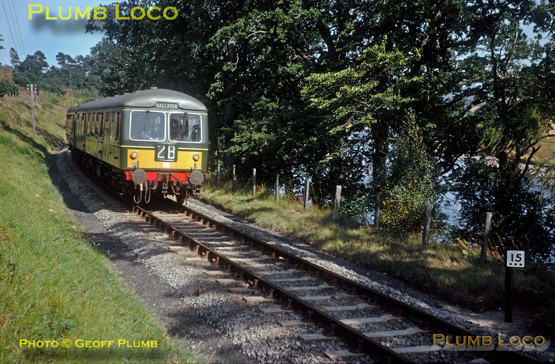 From the Geoff Plumb Collection of original slides. A two-car DMU is running alongside the River Dee and is about to pass milepost 15¾, between Crathes and Banchory, as it works from Aberdeen to Ballater during August 1964. The line closed in February 1966, but part of it is in the process of being reopened. Photographer Unknown. Collect Slide No. 28678.