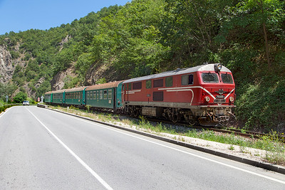 Narrow Gauge Henschel built 75 005 runs alongside the road approaching a level crossingwith train 16105 13.20 Septemvri to Dobriniste. Thursday 7th July 2016.