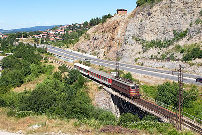 44 098 crosses the River Struma bridge on the outskirts of Pernik with International train 361 15.20 Sophia to Kulata and the Greek border but wth no through coaches. Friday 8th July 2016.