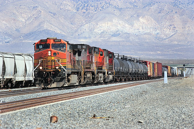 BNSF 4911 (C44-9W), BNSF 575 (B40-8W), BNSF 5464 (C44-9W) & BNSF 8215 (SD75M) have dropped down off the mountain and pass Mojave yard before turning off towards Barstow. Sunday 29th April 2007.