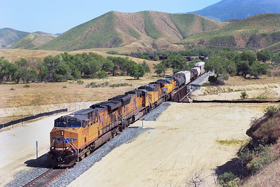 UP5372, UP5832 & UP 5404 (all C45ACCTE) with their 130 wagon manifest train are now off the mountain and pass over Ilmon Caliente Creek. Work is underway to install double track over this section between Bena and Caliente. Friday 27th April 2007.