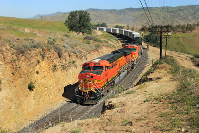 BNSF 7661 (ES44DC), BNSF 511 (B40-8W) & FURX 8054 (SD40-2) head a eastbound intermodal towards tunnel 3 on the exit from Bealville. 27th April 2007.