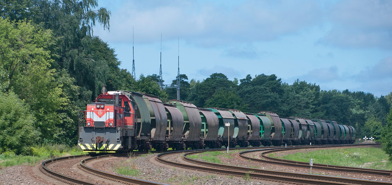 Shunter slowly takes a long train of hoppers off the branch to the northern docks in the direction of Klaipeda station.<br /> <br /> Addicted to the sound of these basic wagons as they clank by.<br /> <br /> 29th July 2017