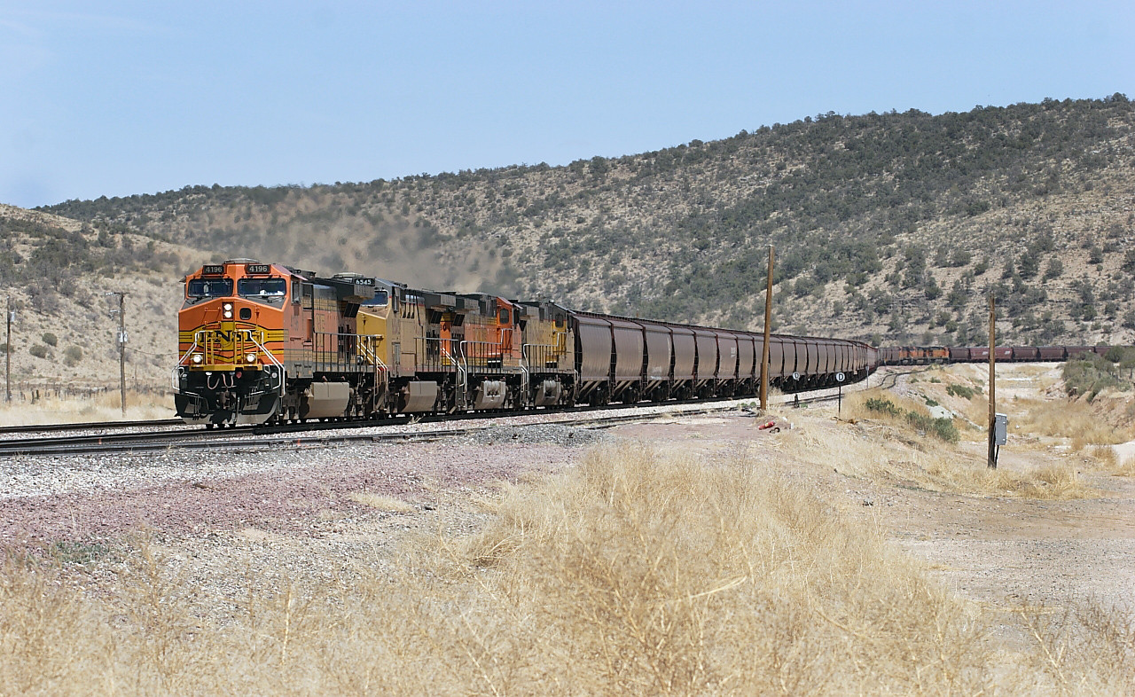 BNSF 4196 (C44-9W), UP 6545 (CC44AC), BNSF5230 (C44-9W) & UP 9720 (C44-9) with mid train helpers BNSF 4096, BNSF 5222 & BNSF 5342 (all C44-9W's) visible and rear end helpers BNSF 5289 & BNSF 730 (both C44-9W's) out of site passing Peach Springs with the westbound loaded grain train, which at the time was the longest and  heaviest train on the network. To me this scene the train is passing through screams AT & SF territory. 02/05/2007.