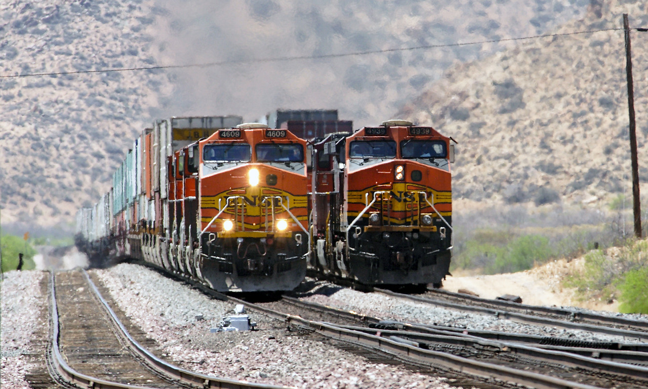 BNSF 4609, BNSF 1083, BNSF 5843 & BNSF 4754 (all C44-9W's) storm past BNSF 4939 plus 3 other Dash 9's, both eastbound doublestack trains at East Valentine.  This shot also shows how American railways tend to follow the lie of the land without to much cut and fill as in the UK. 02/05/2007.