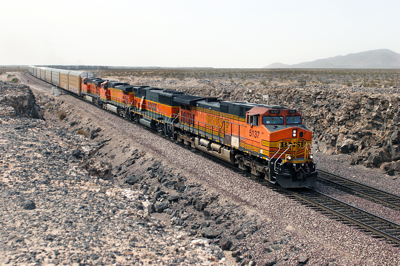 BNSF 5137 (C44-9W), BNSF 343 (GP60B), BNSF 4165 (C44-9W) & BNSF 7638 (ES44DC) have their eastbound train of Autoracks stretched out across the desert behind them as they pass Ash Hill. 04/05/2007.