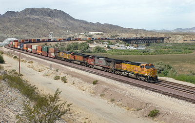 BNSF 5396, BNSF 746 (both C44-9W's), BNSF 5852 (ES44AC) & UP 5999 (C44ACCTE) cross the Colorado River bridge at Topock and are now in Arizona with an eastbound doublestack train. BNSF 5396 is suffering from the paint pigment problem and it has become known as the Pumpkin livery. 01/05/2007.