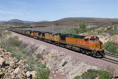 BNSF 4196 (C44-9W), UP 6545 (CC44AC), BNSF5230 (C44-9W) & UP 9720 (C44-9) with the westbound loaded grain train have just exited Crozier Canyon and rounded the 90 degree curve and heading towards Crozier. The mid-train helpers are hidden behind the hill in the middle distance and the rear train helpers are still in the canyon on the right showing how long this train really is. This view is taken from the roadside with the Music Mountains in the background. 02/05/2007