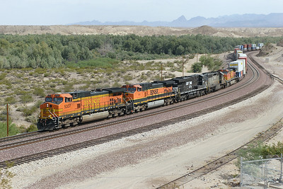 BNSF 5307, BNSF 1011 (both C44-9W's), NS 7630 (ES40DC), HLCX 6227 (SD40-2) & BNSF 4733 (C44-9W) are heading west out of the Sacramento Wash and approaching the Colorado River bridge at Topock with a doublestack train. HLCX 6227 is Ex QNSL 260 and is fitted with an oversize fuel tank. 01/05/2007.
