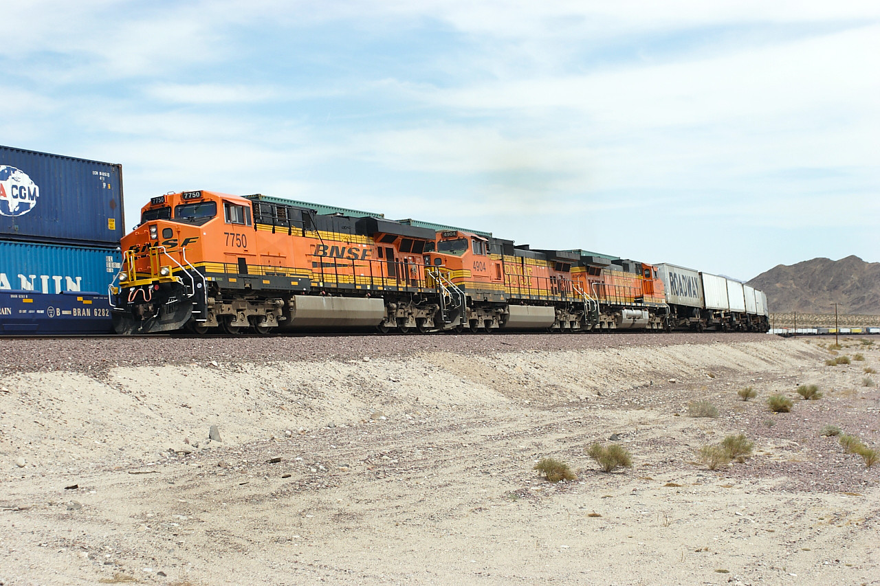BNSF 7750 (ES44DC), BNSF 4904 & BNSF 4066 (both C44-9W's) storm past the slow moving BNSF 738 with a hotshot intermodal westbound at Siberia. 30/04/2007.