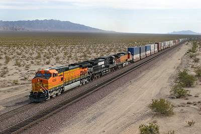 BNSF 4090 (C44-9W), NS 9378 (C40-9W) & BNSF 4733 (C44-9W) head through the desert at Essex with an eastbound doublestack train. 30/04/2007.