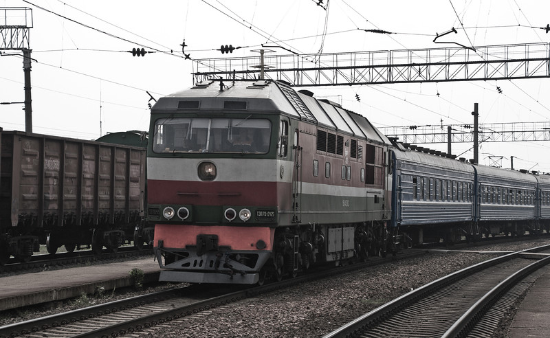 One of the massive TEP 70 diesels on a passenger train heading into Minsk passes a freight train heading the other way