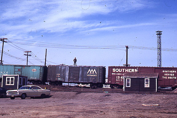 A brakeman rides the top of a boxcar at the hump yard of the Boston and Maine RR. This photo was taken in the early seventies before safety rules were changed to prohibit  employees riding the tops of cars