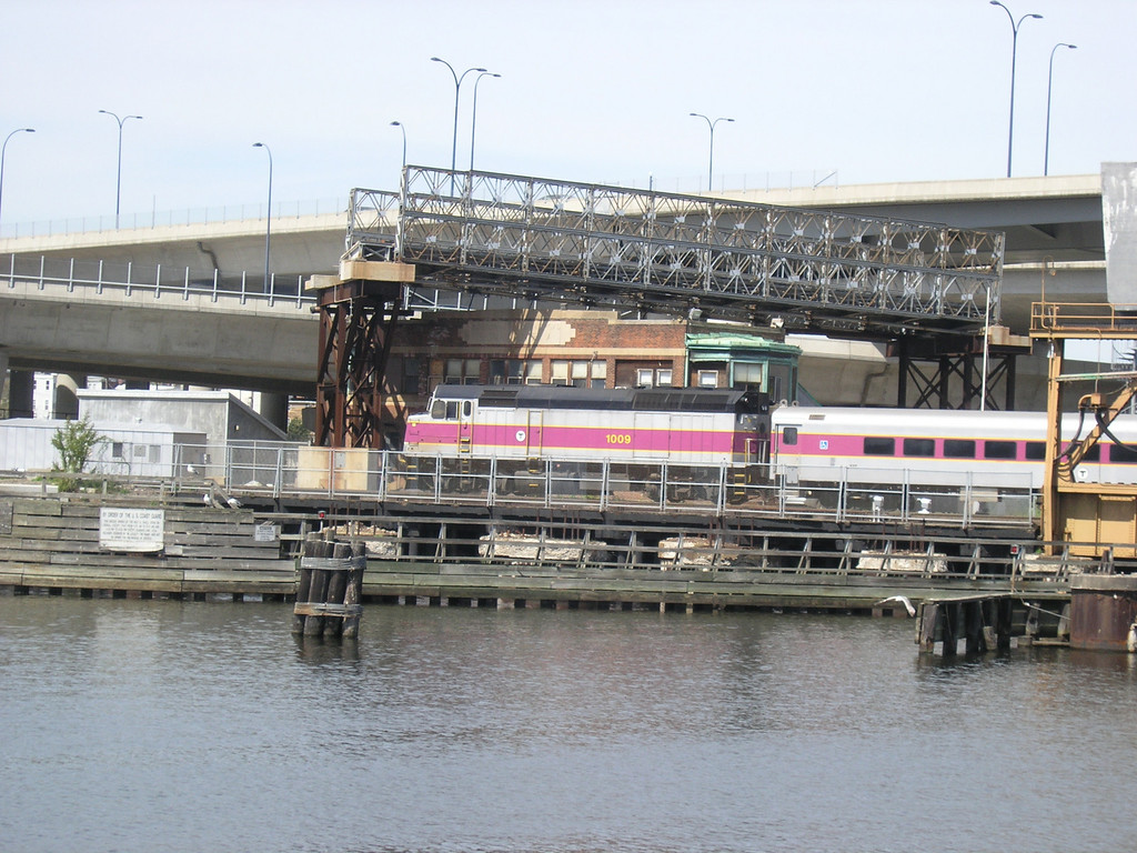 "MBTA Engine number 1009 operating in ""push-pull"" mode is pushing a commuter train into North Station over a Charles River drawbridge.     Signal Tower A in the background is one of the few surviving buildings with the words ""Boston and Maine Railroad"" carved into it. The Boston and Maine once dominated transportation north of Boston but it no longer operates passenger trains and its freight business is only a shadow of what it once was. Note the remant on one the Big Dig's temporary roads over the roof of Tower A."