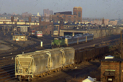 Boston, MA - Near the engine terminal - Date not recorded - Former Burlington Northern engine still in BN Cascade green paint. The three Budd RDC's are functioning as coaches, by this time they no longer ran on their own power.
