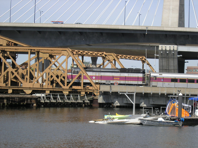 MBTA Engine 1009 pushing an inbound commuter train on the North Station draw bridge over the Charles River.  This is May 2006. The small boats in the foreground belong to the Spaulding Rehab. Hospital which uses them for physical therapy.