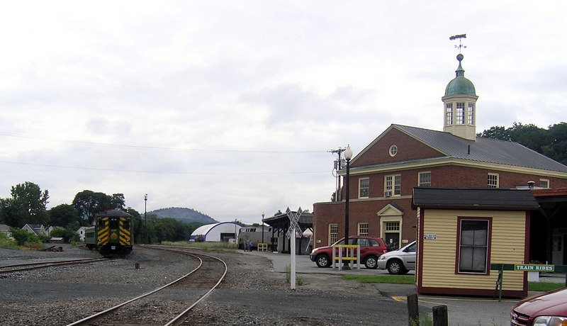 White River Junction, Vermont - The engineer of Amtrak's southbound Vermonter has left his cab for a few minutes to chat with 2 railfans on the platform. The old green coaches on the left are for the Green Mountain Railroad's summer only tourist train to Thetford, VT      8/25/2006