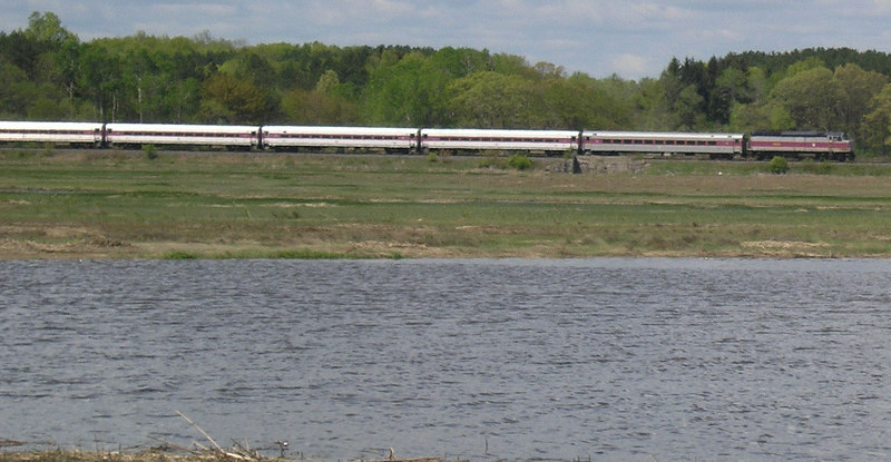 OLYMPUS DIGITAL CAMERA      . . . . May 24, 2006 . . . Newbury, MA - - - Train 161 running through the salt marshes next to the Little River, next stop Newburyport. This MBTA line started life as the Eastern Railroad and was for a long time the Eastern Route of the Boston and Maine RR Portland Division. It is over half a century since the last train traveled the entire route Boston to Portland but passenger trains run as far a Newburyport.