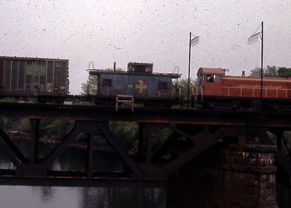 The Merrimack River Bridge at Haverhill, MA - Otter Valley RR switch engine being hauled by a B&M freight train.